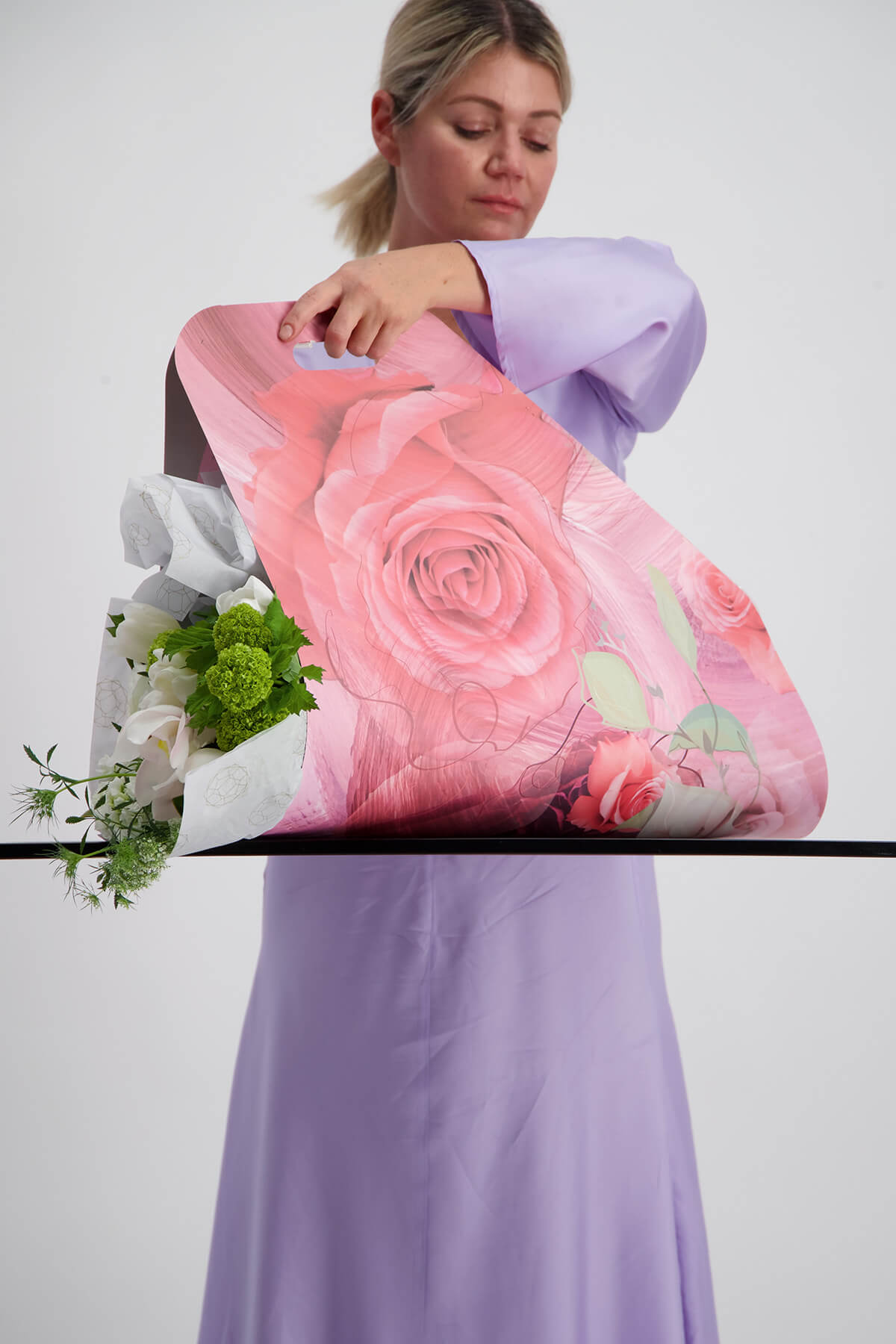 Florist holding bunch of white and green flowers wrapped in pink packaging during a photoshoot