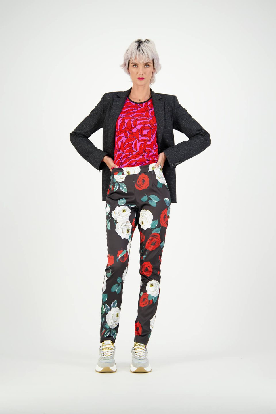 Women's fashion model studio photoshoot wearing floral pants, red tee and black blazer over the top