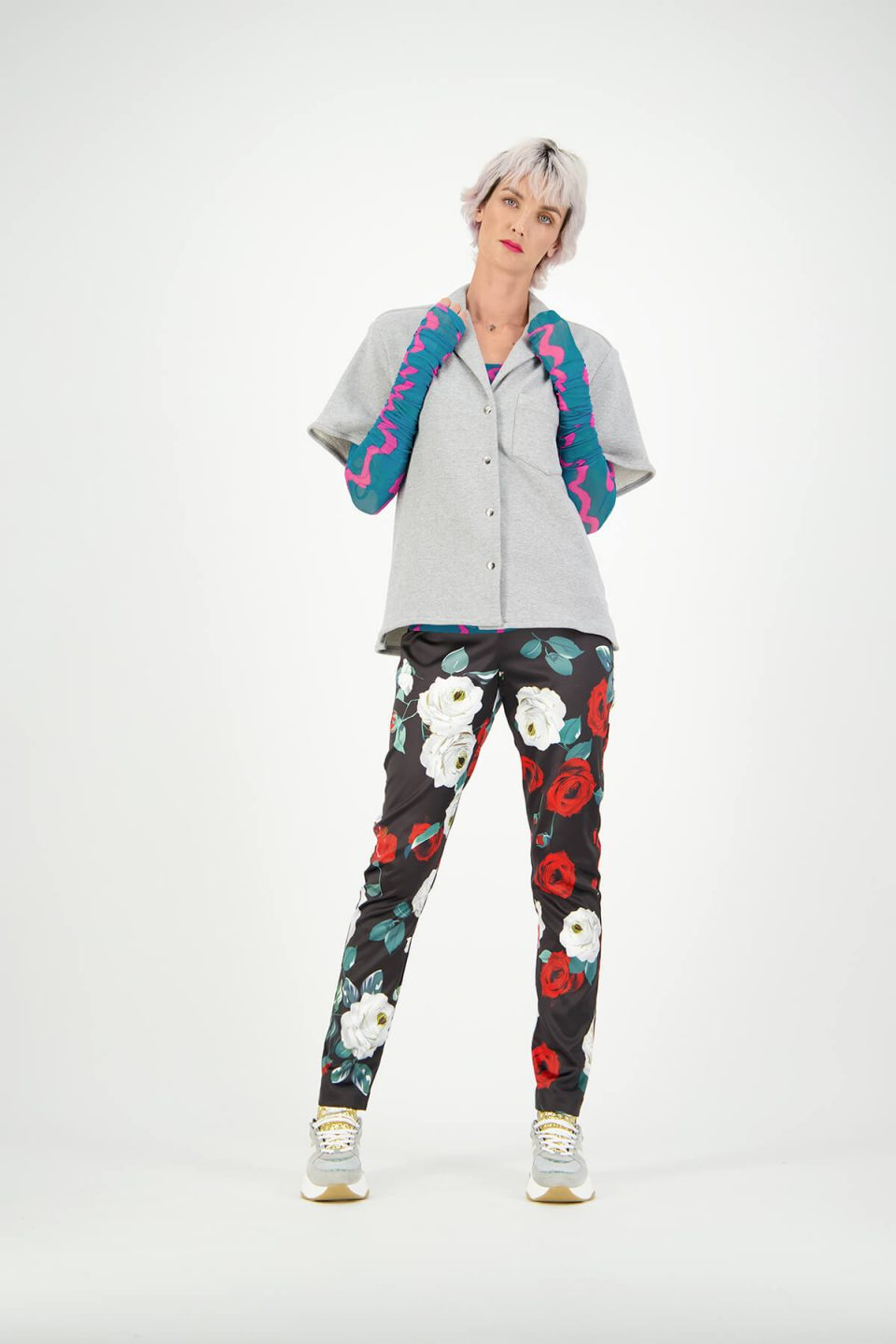 Women's fashion model studio photoshoot wearing floral pants and grey button up tee-shirt
