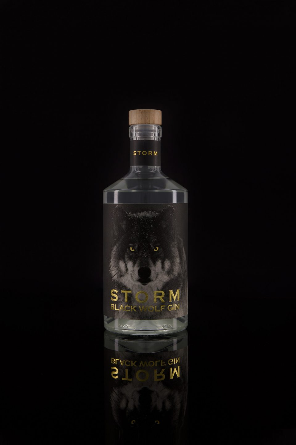 STORM Gin photographed on black background with gold reflections